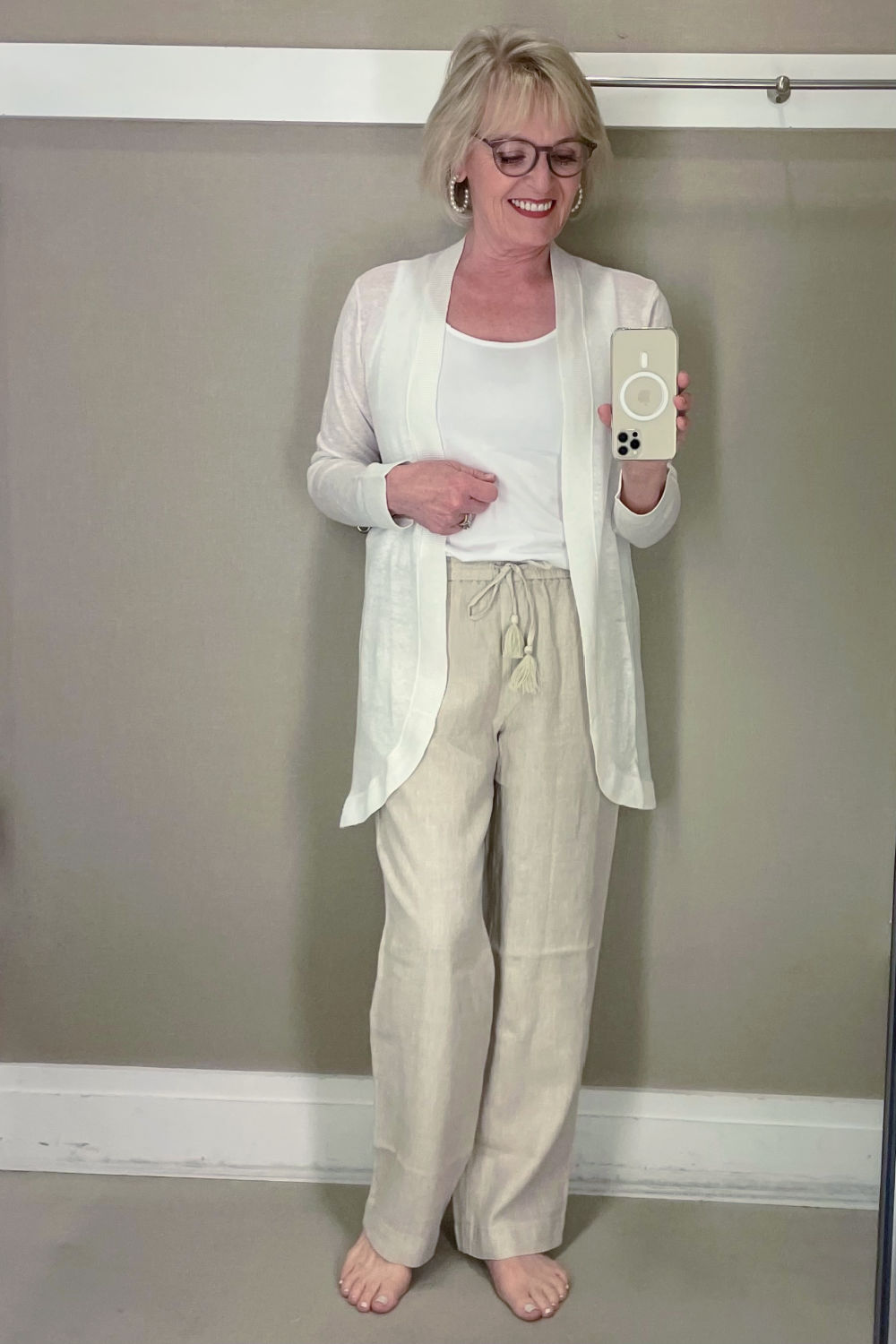 WOMAN TAKING SELFIE IN DRESSING ROOM WEARING WHITE CARDIGAN AND LINEN PANTS