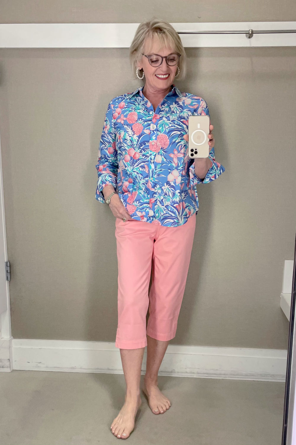 blonde woman talking selfie in dressing room mirror wearoing floral shirt and pink chinos