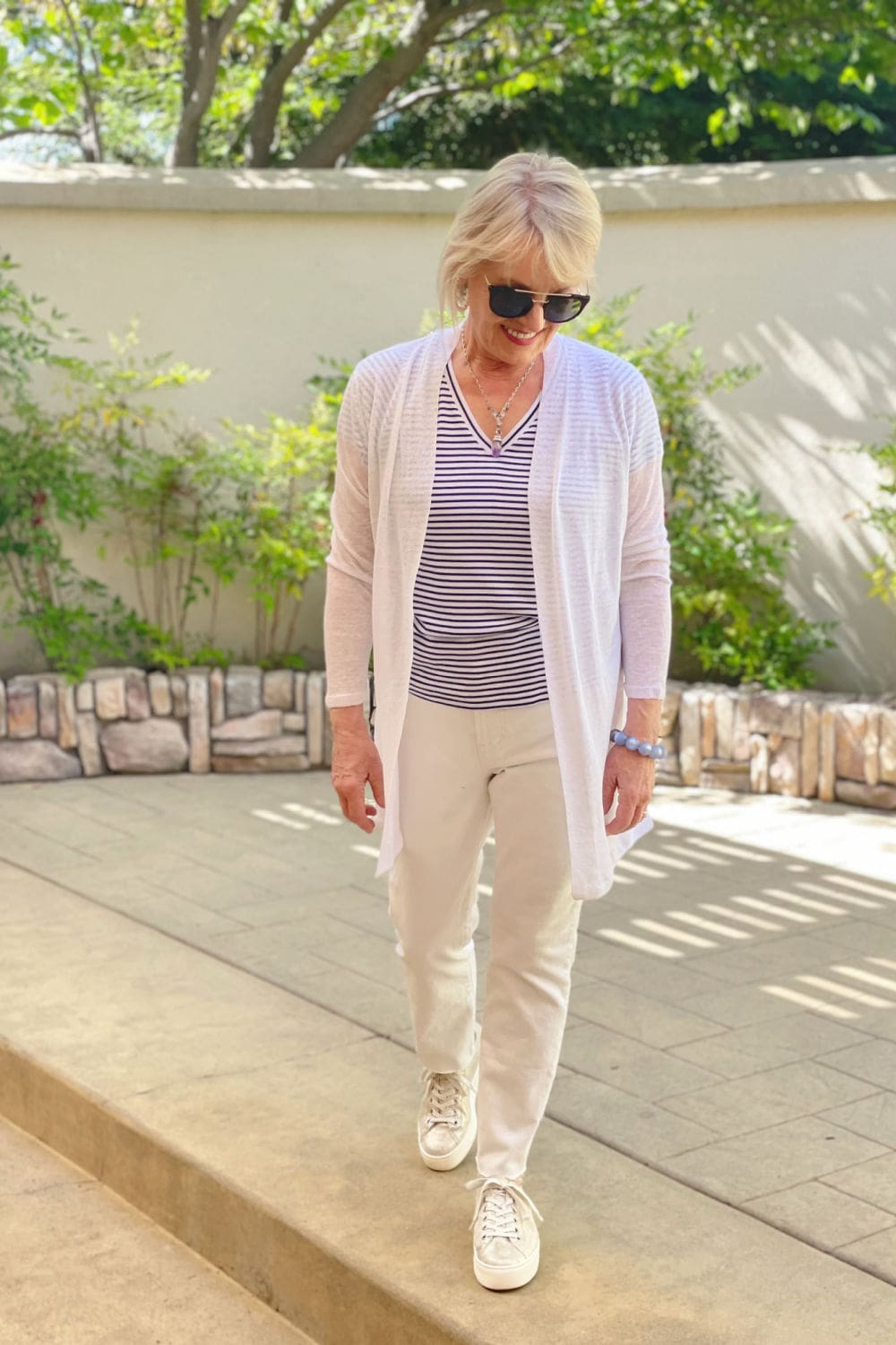 woman walking in courtyard wearing modern white jeans and striped tee