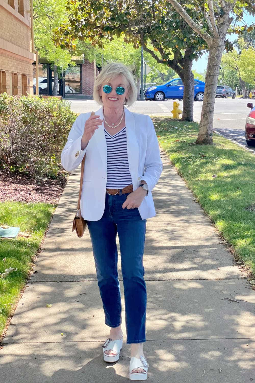 woman walking towards you on sidewalk with mirror sunglasses, white blazer and blue jeans