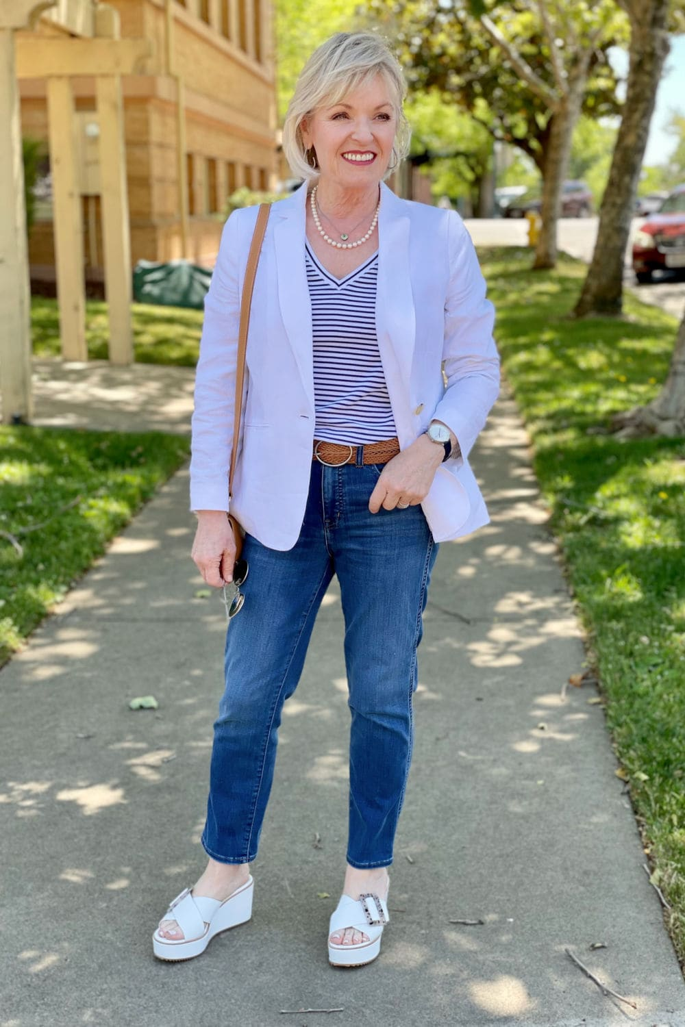 over 50 fashion blogger jennifer of a well styled life standing on sidewalk under tree wearing white linen blazer and blue jeans