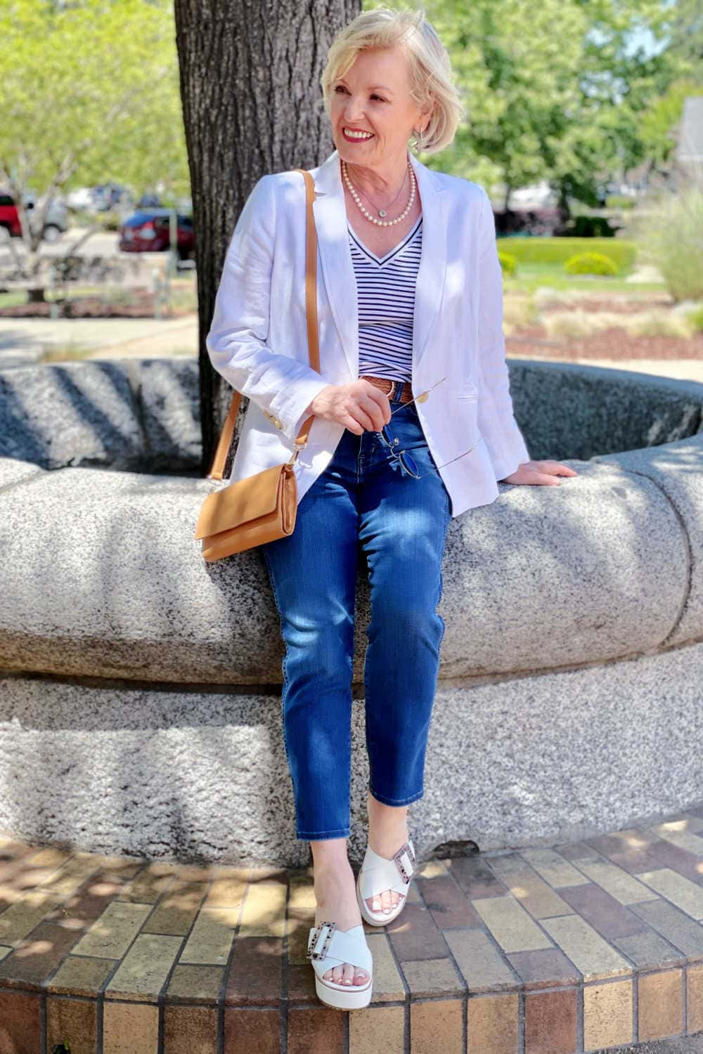 woman sitting on cement wall wearing jeans, blazer and striped tee