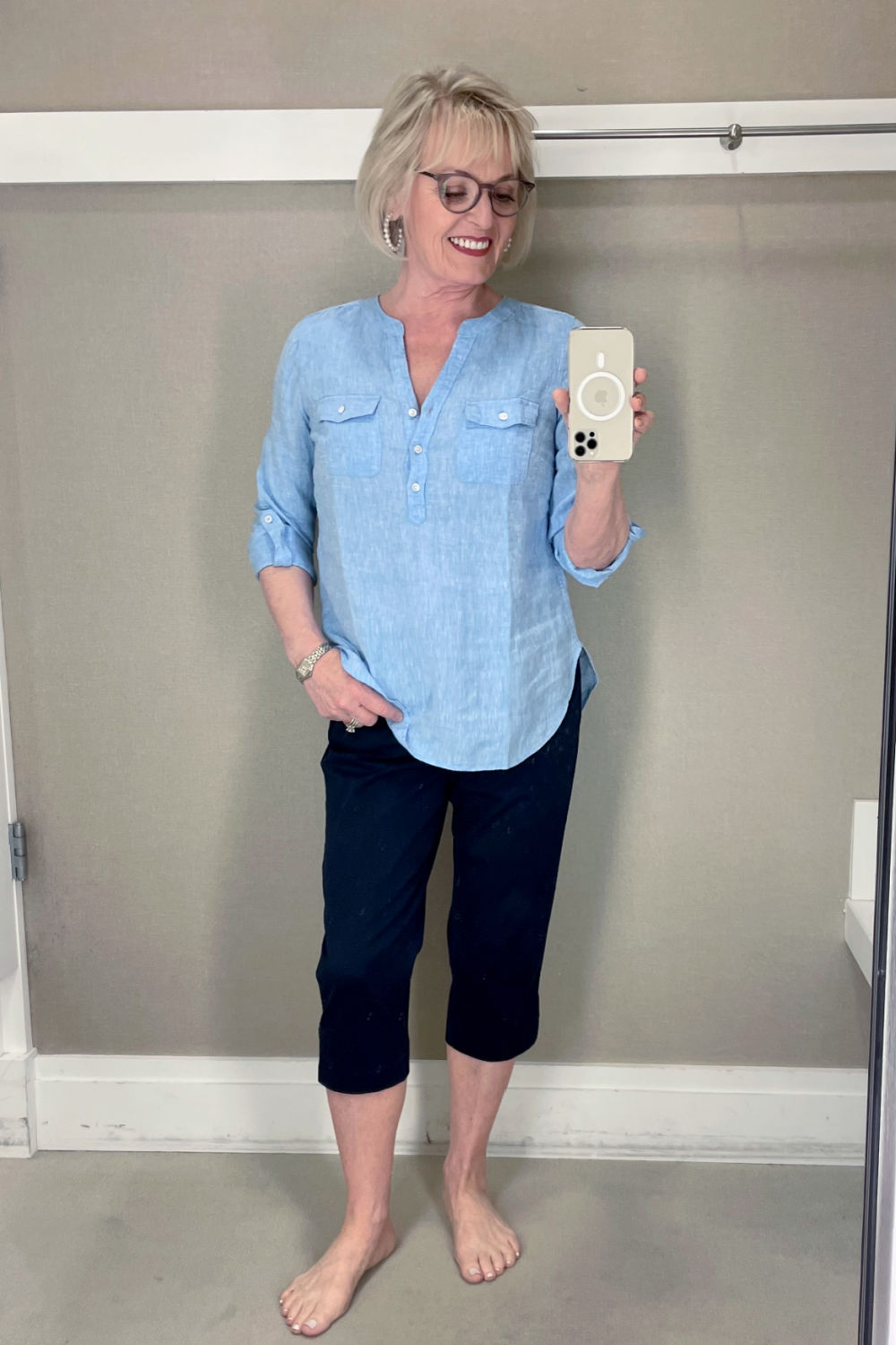60 year old woman wearing blue shirt and cropped pants in dressing room