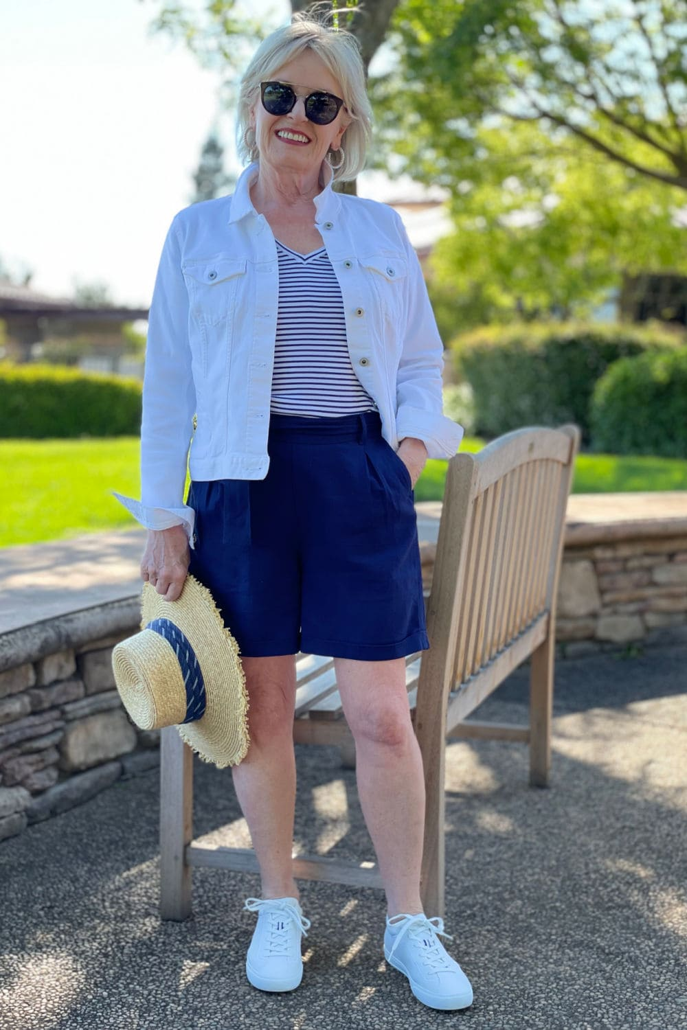 jennifer of a well styled life wearign navy pleated shorts and rothy's sneakers
