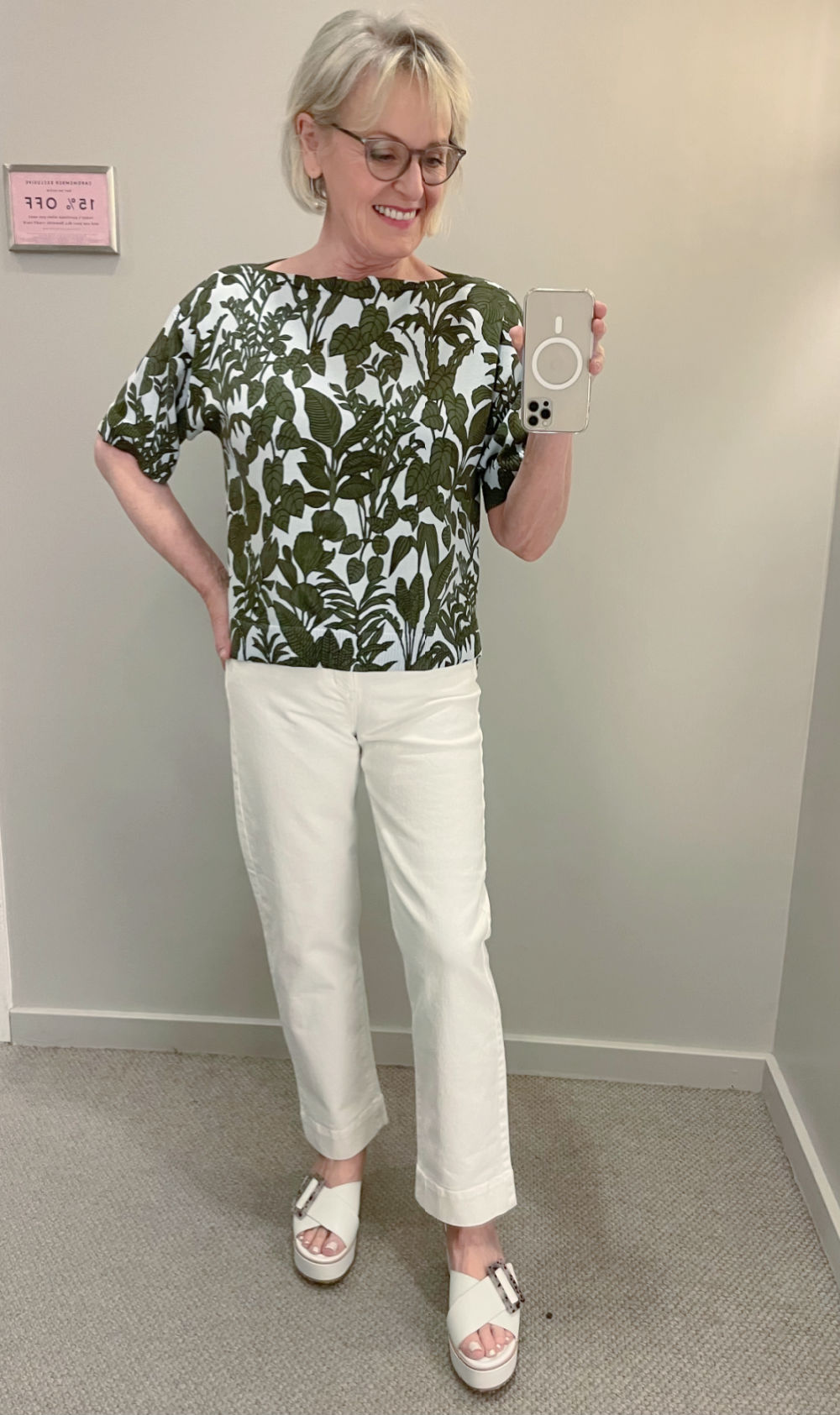 woman wearing botanical sweater and wide leg jeans in changing room