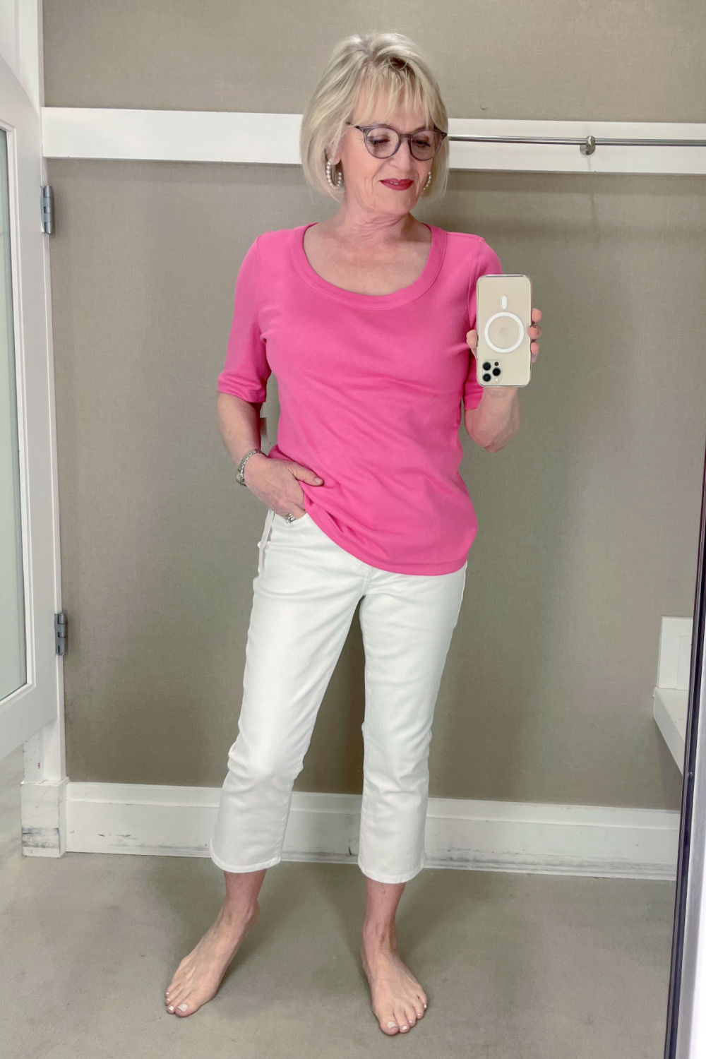 over 50 woman trying on wuite crop flare jeans with pink top