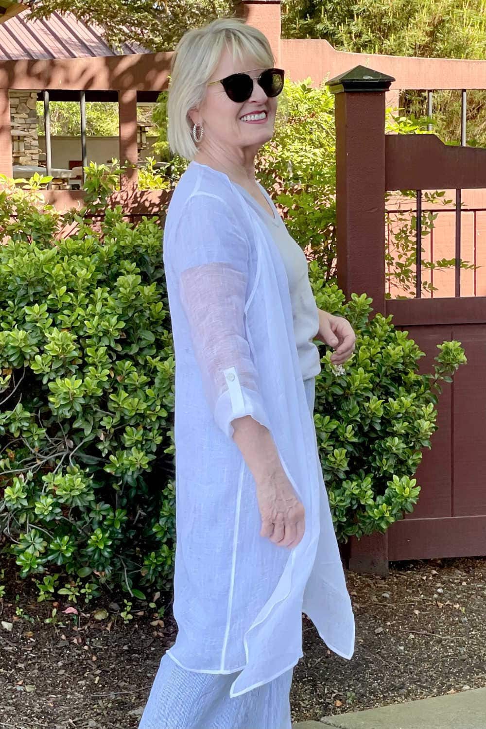 side view of woman showing tab button detail on sleeve of linen topper