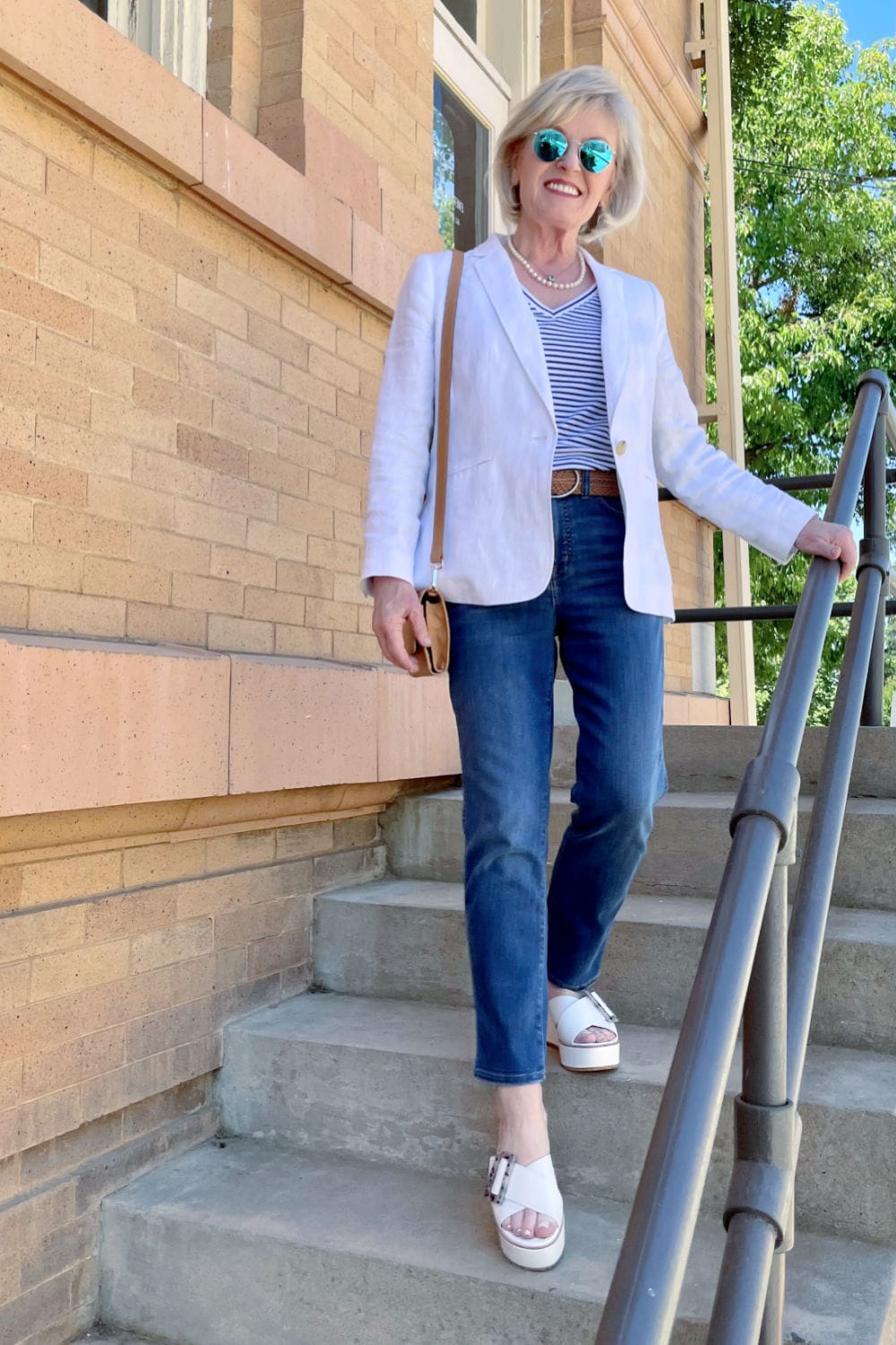 blonde woman walking downstairs weaing linen blazer and blue jeans with white sandals