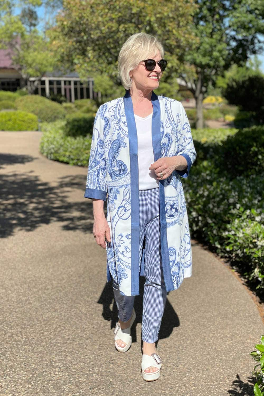 woman walking in sun wearing white tee, blue and white kimono and blue and white houndstooth pants