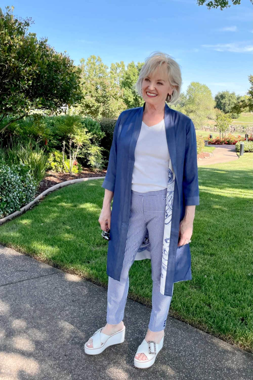 blond woman wearign blue duster and plaind pants with white shoes