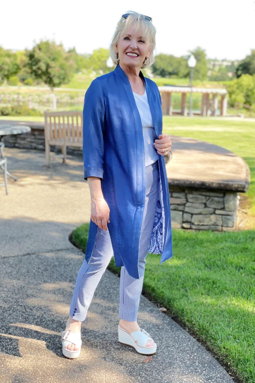 over 50 blogger modeling blue jacket and plain pants in park