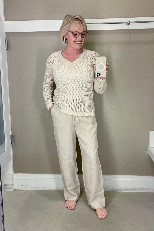 blonde woman taking selfie in mirror wearing beige sweater and pants
