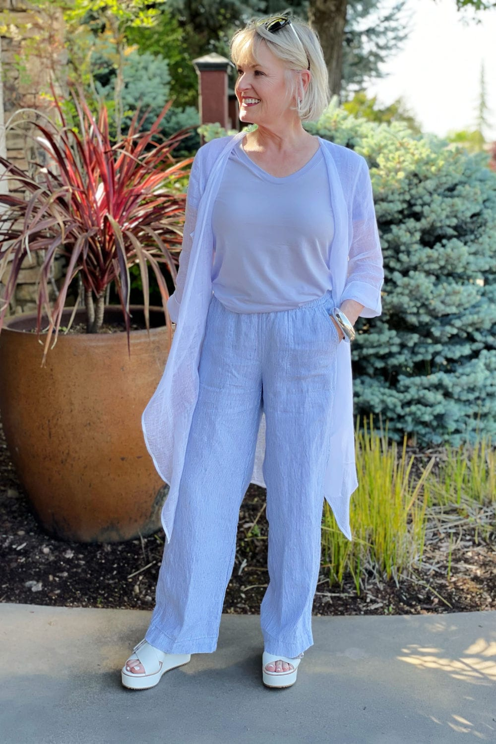 jennifer of a well styled life wearing purple tee, linen cardigan and line pants in front of gate