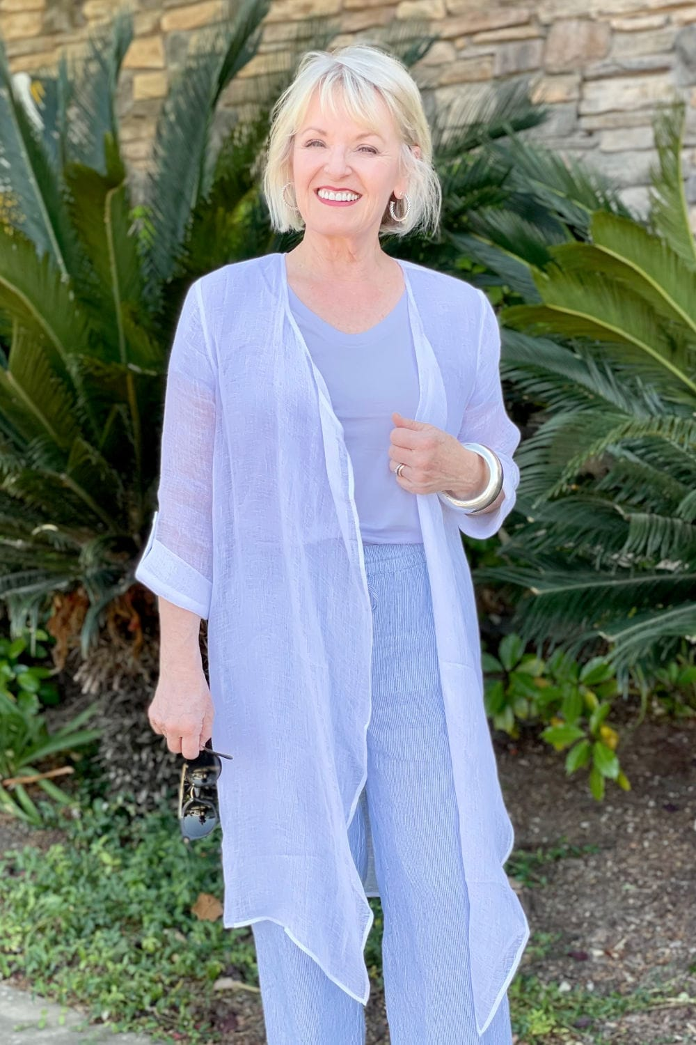 woman wearing linen cardigan over purple top standing in front of sago palm