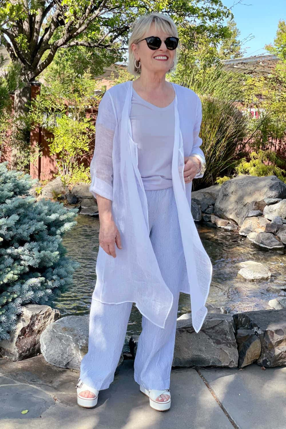 woman standing ion frotn of fountaion wearing gauzy linen duster and linen pants