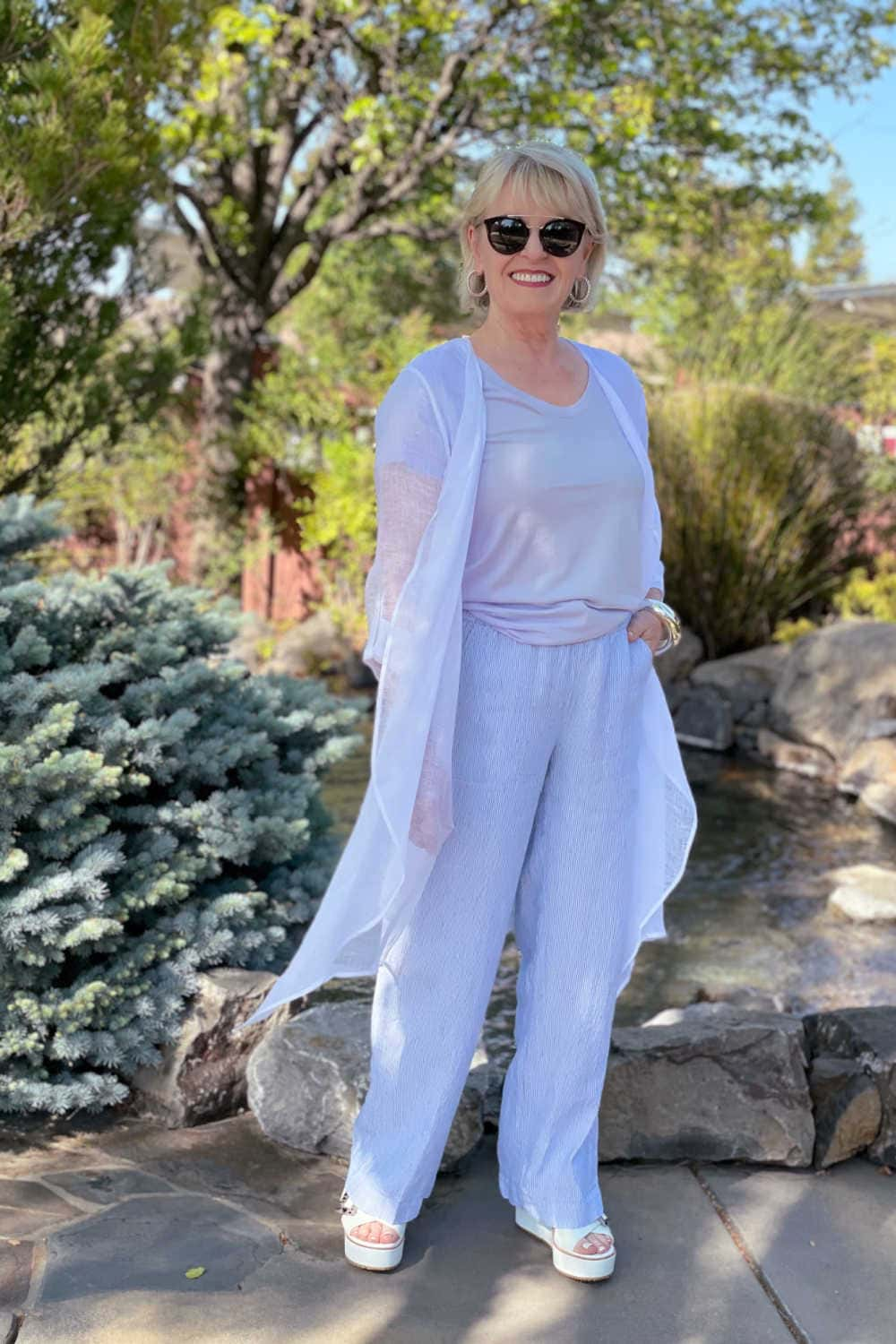 woman standing in front of pond wearing white gauze duster with striped linen trousers