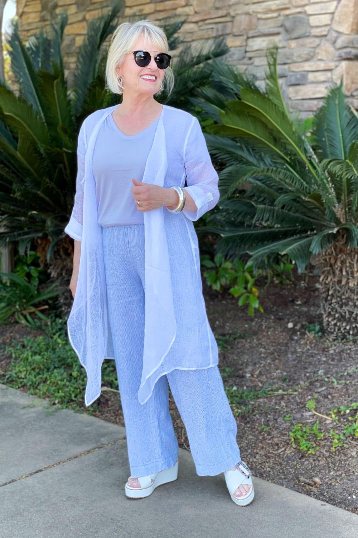 over 50 blogger modeling white guaze topper and linen pants
