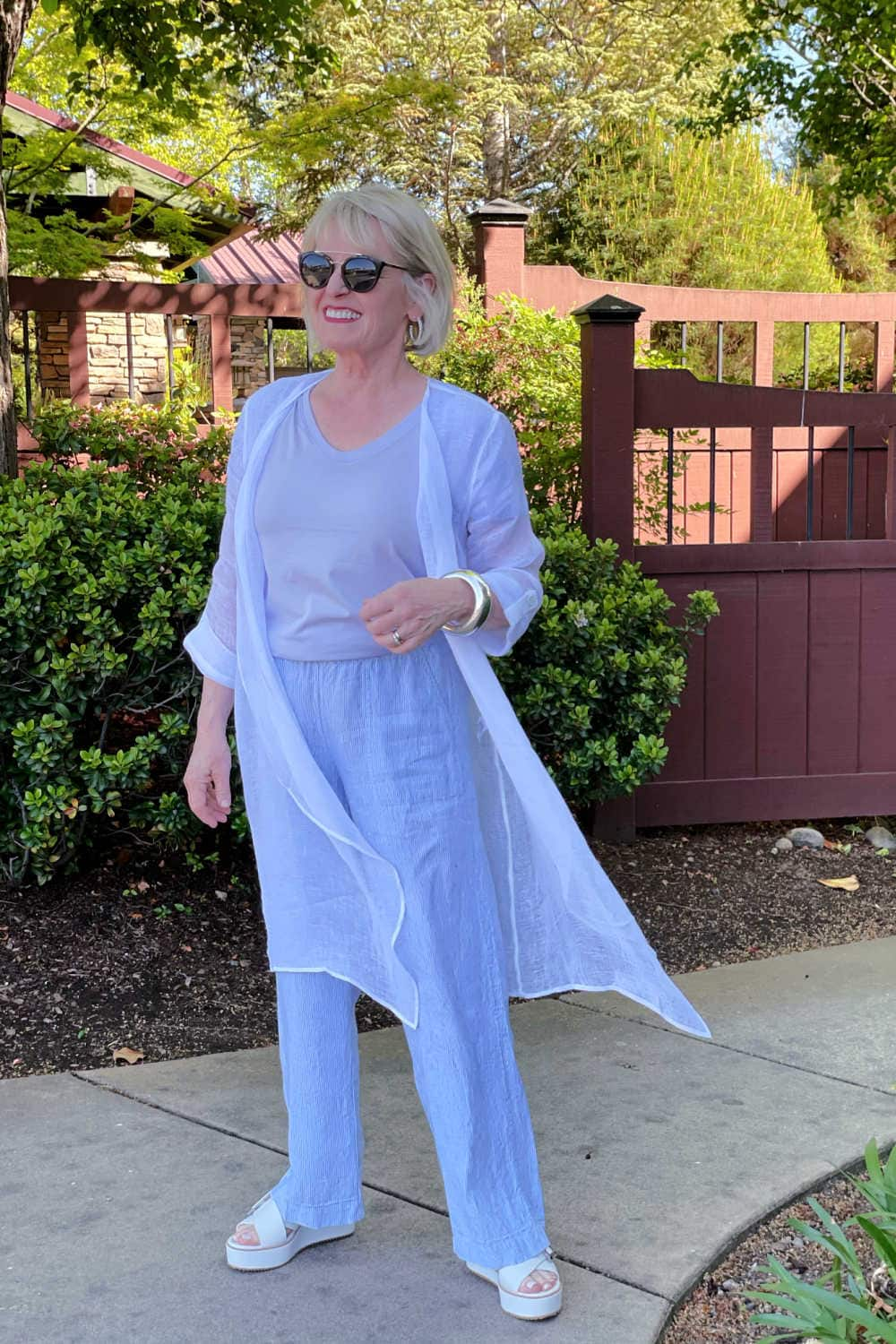 woman wearing linen duster with striped linen pants