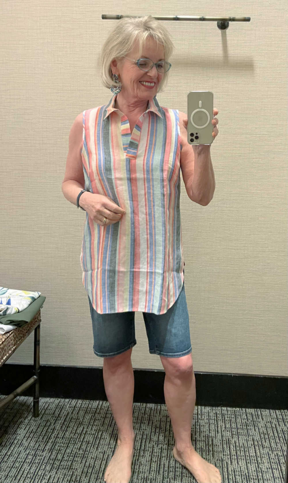woman taking selfie wearing striped linen tunic and shorts