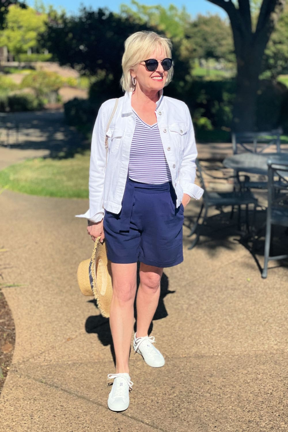 over 50 blogger wearing navy shorts with white sneakers and striped tee
