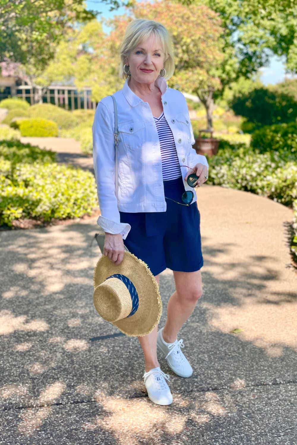 woman wearing navy linen shorts and white denim jacket