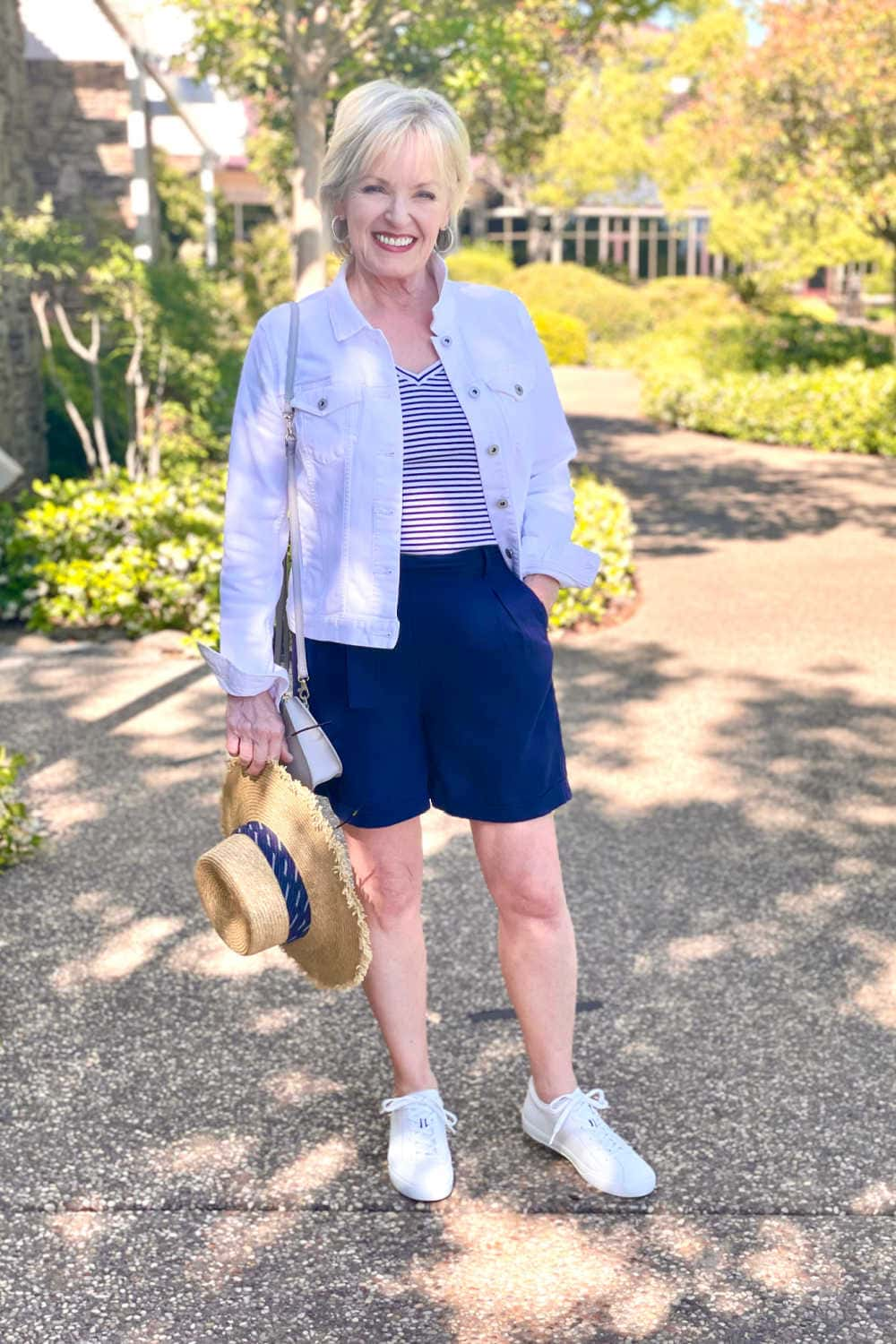 woman wearign whte denim jacket, navy pleated shorts and white sneakers