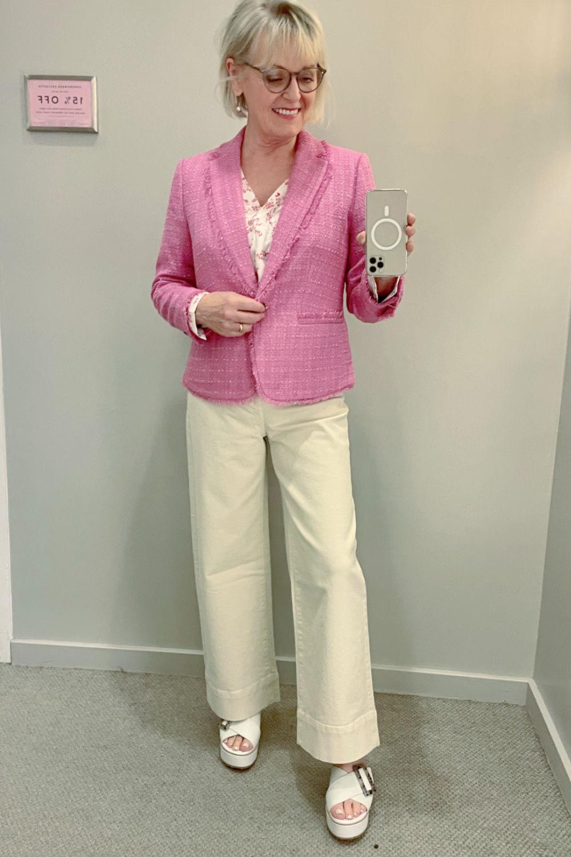 mirror selfie of blonde woman wearing pink blazer and beige jeans at ann taylor