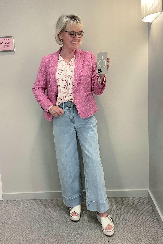 woman wearing pink tweed blazer and winde leg denim jeans in dressing room