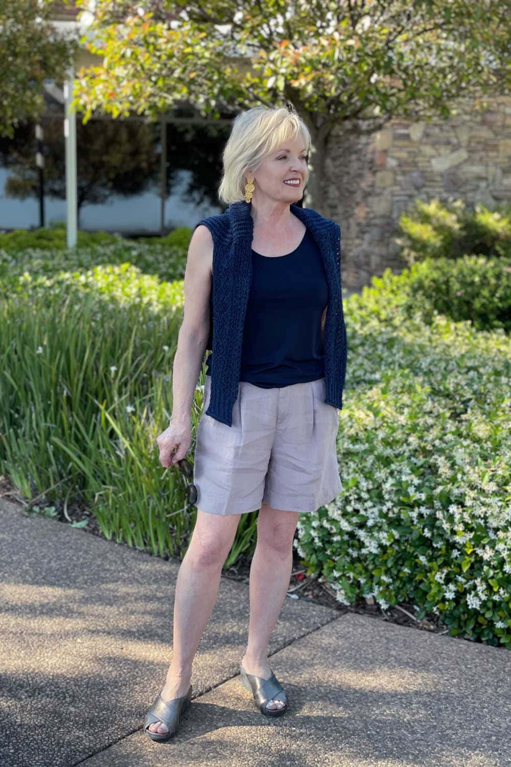 woman standing on path wearing navy blue open weave sweater and shorts