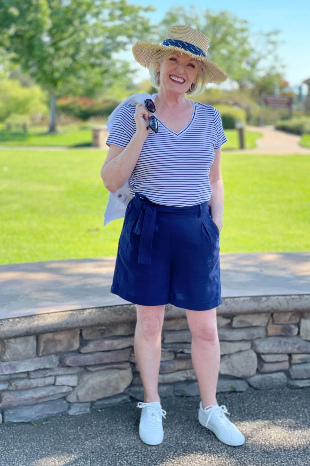 blond women over 60 wearing striped tee and navy belted shorts