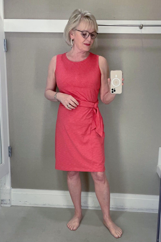 blonde woman taking selfie in mirror wearing red dress