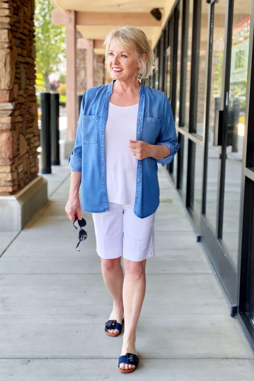 woman walking at shopping center weagn white shorts and denim shirt