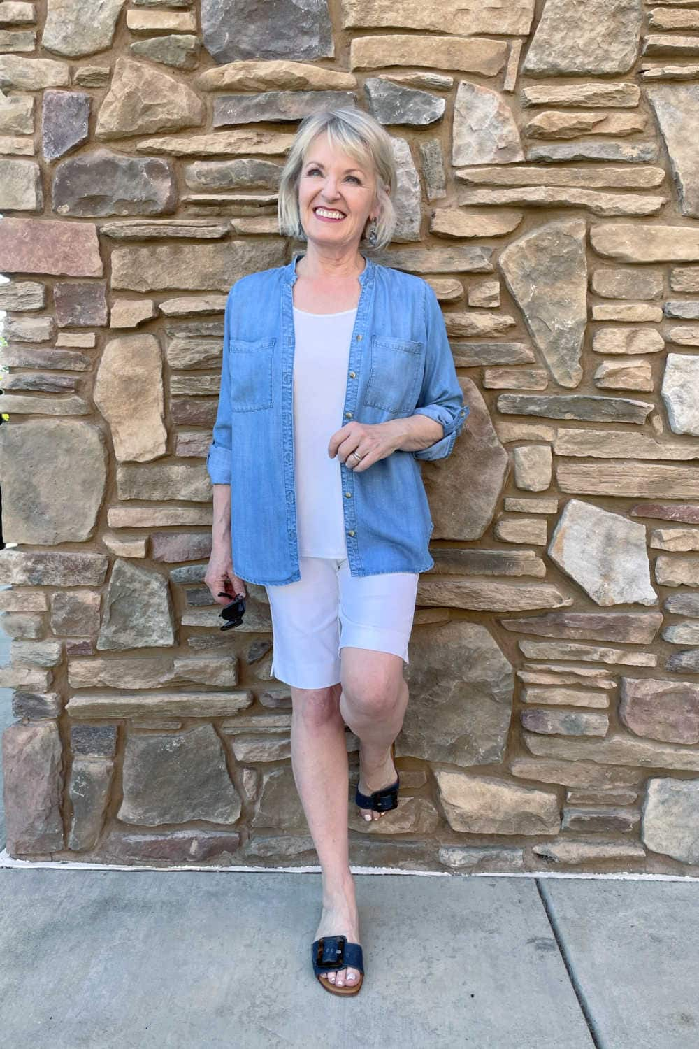 woman leaning against wall wearing denim top and stretch shorts