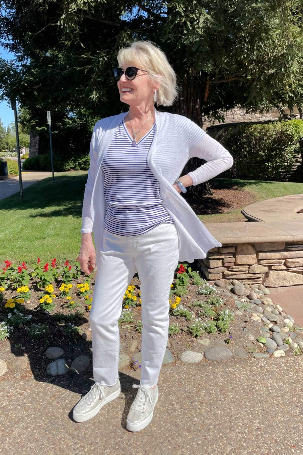 woman standing in front of tree wearing white jeans, striped tee and metallic sneakers
