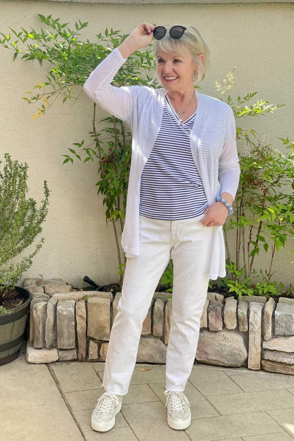 woman raising sunglasses to look under wearing white jeans and striped tee