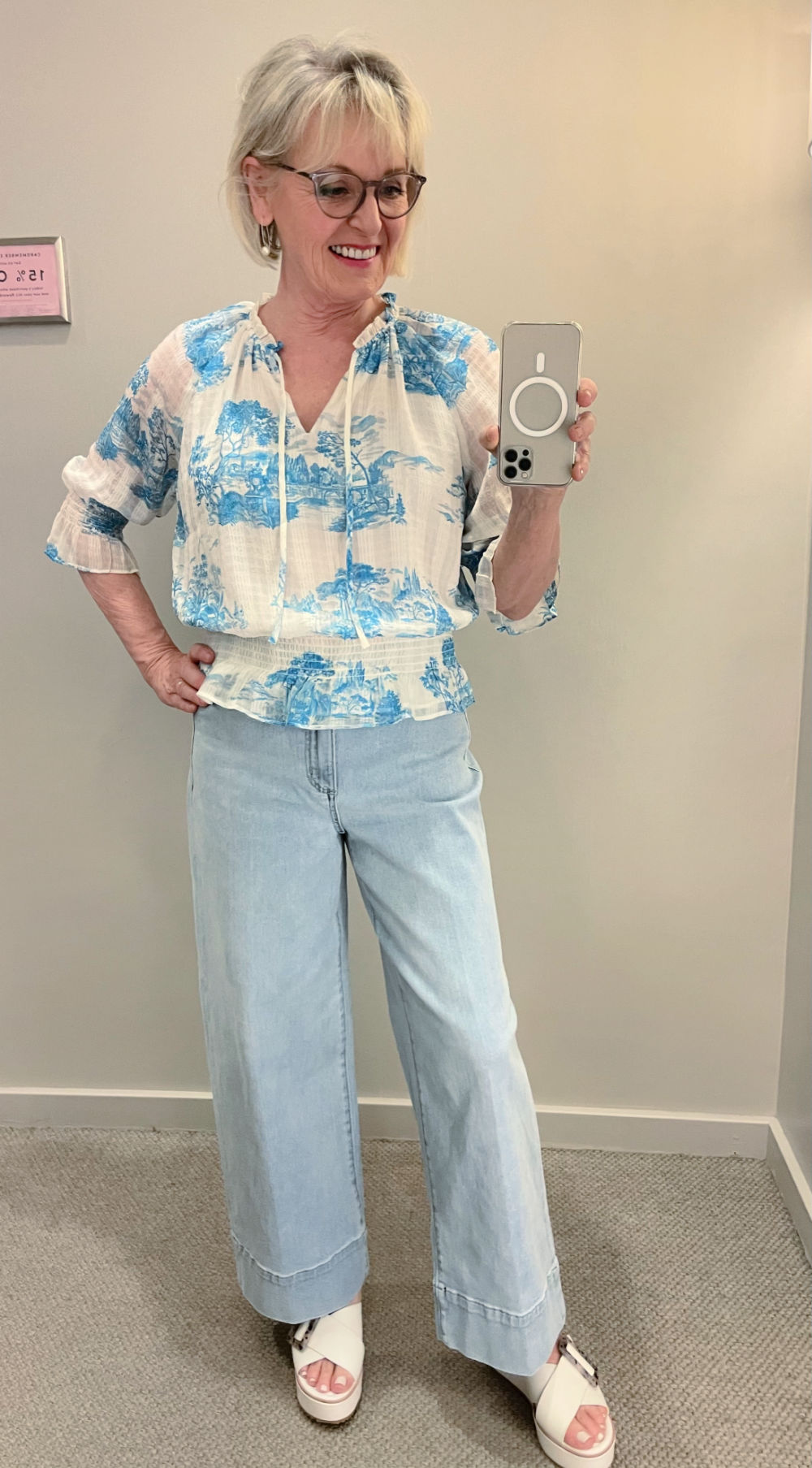 blonde woman taking dressing room selfie in toile blouse and jeans at ann taylor