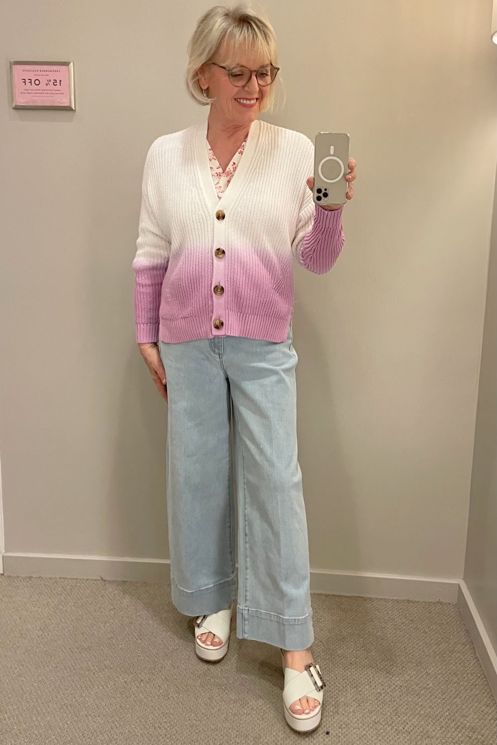 woman wearing varigated cardigan and wide leg jeans in dressing room mirror