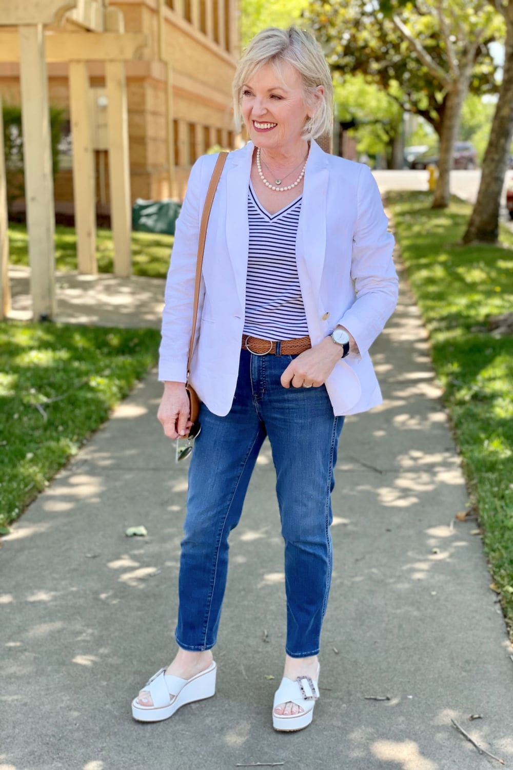 woman on sidewalk smiling at camera wearing mirrored sunglasses, jeans and striped tee
