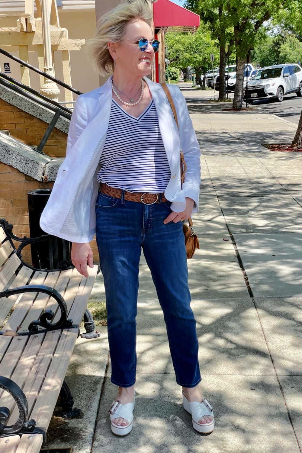 woman walking down street in striped tee, blue jeans and white jacket