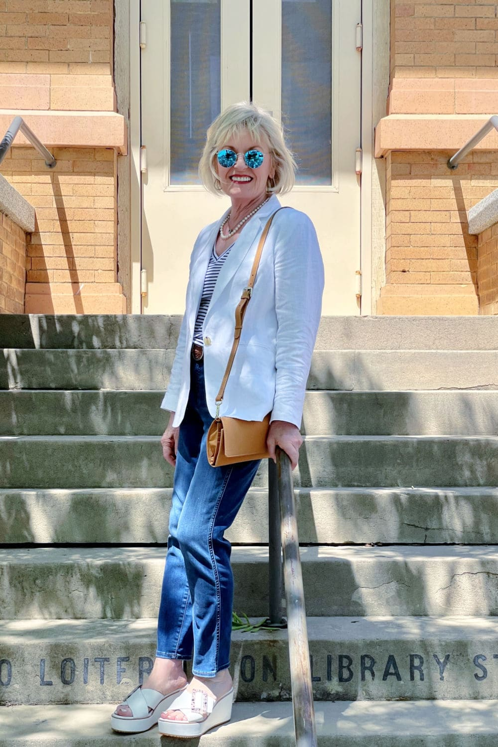 blonde woman leaning on railing os strair wearing white blazer and blue jeans