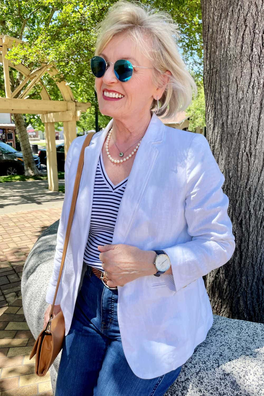 woman wearing striped tee, white blazer and pearls sitting by tree