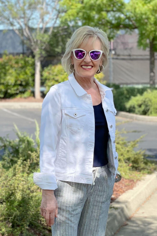 woman wearing white mirrored sunglasses, navy top and white denim jacket