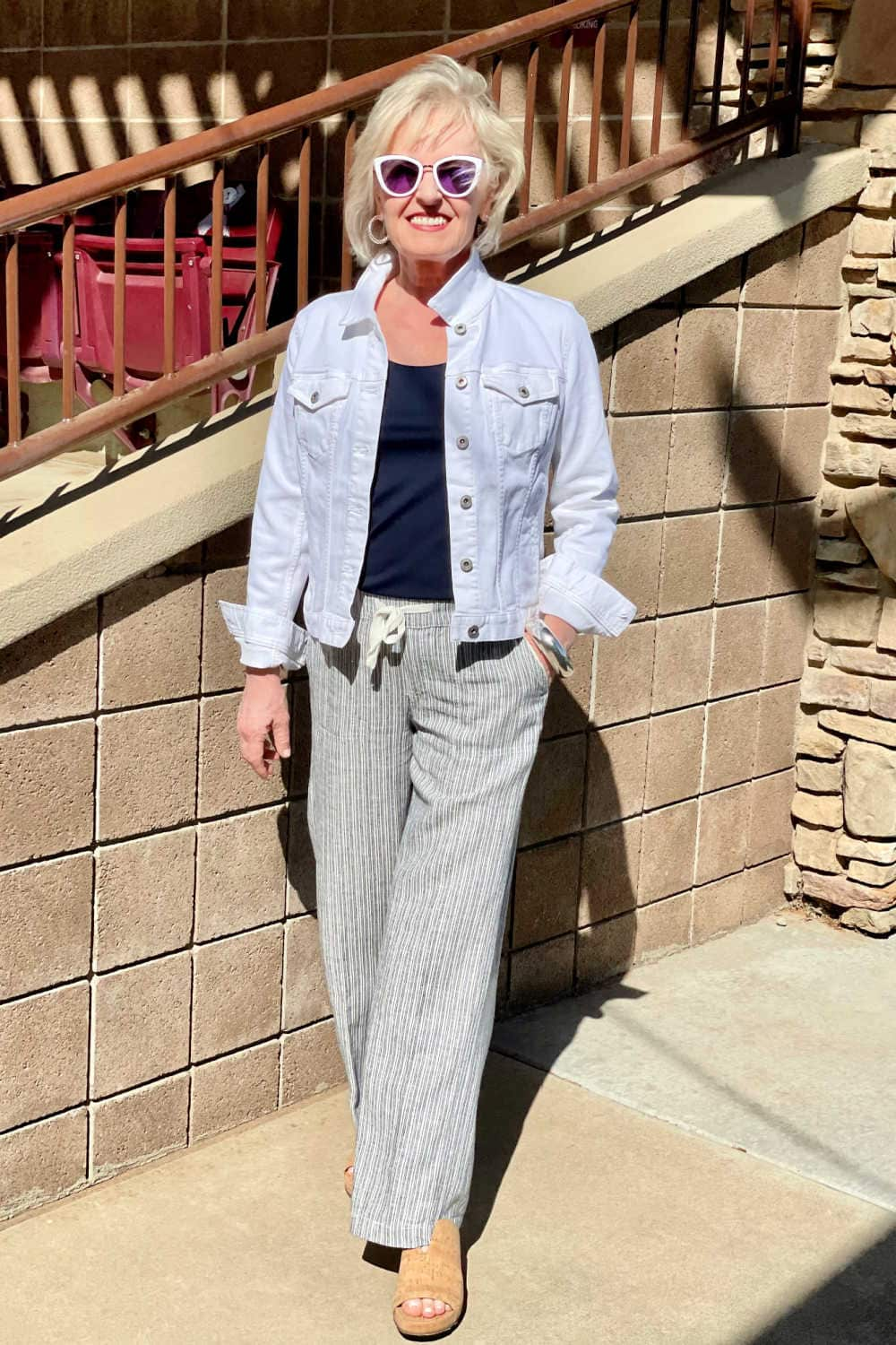 woman walking toward the camera wearing mirrored sunglasses, white jacket, striped pants and cork shoes