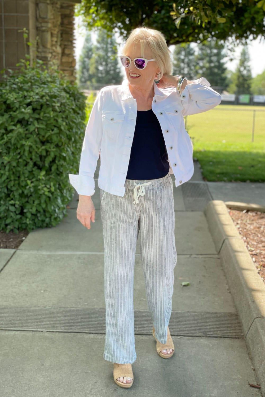 woman walking on path adjusting collar of white denim jacket