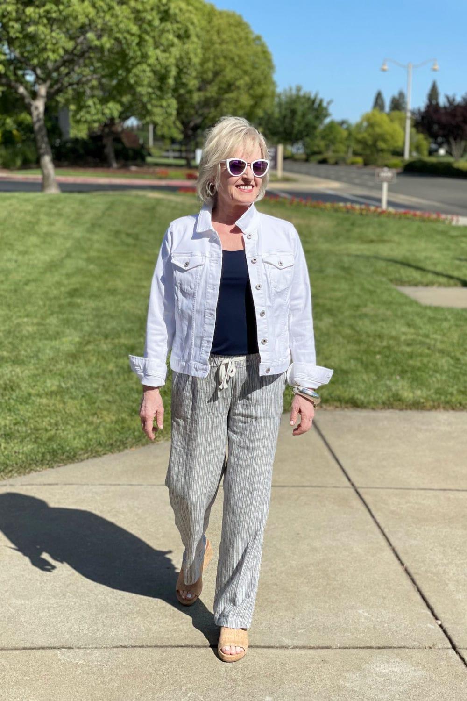 blonde wonman walking down sidewalk wearing white denim jacket and navy linen pants