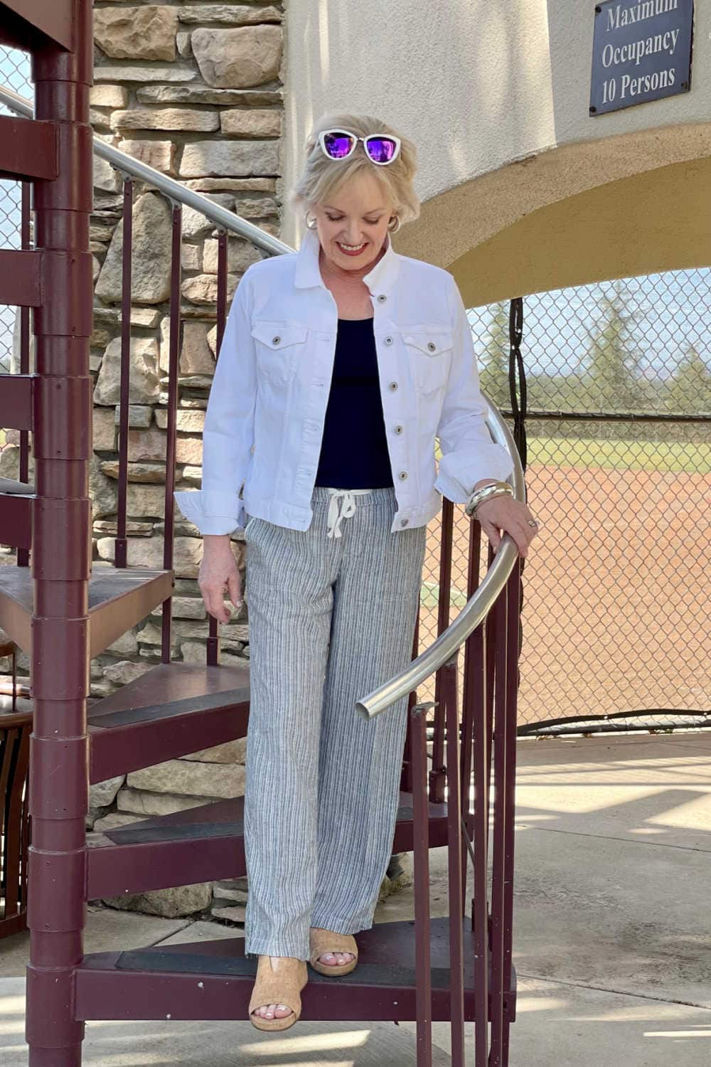 blonde woman walking down spiral staircase wearing white jacket, striped pants and cork wedges