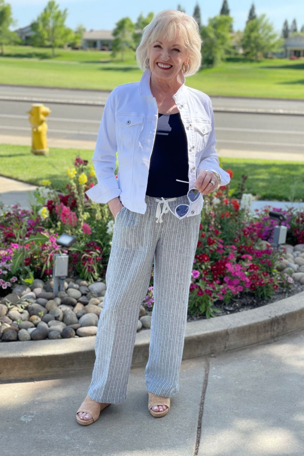 woman standing in front of flower bed wearing white denim jacket and striped linen pants