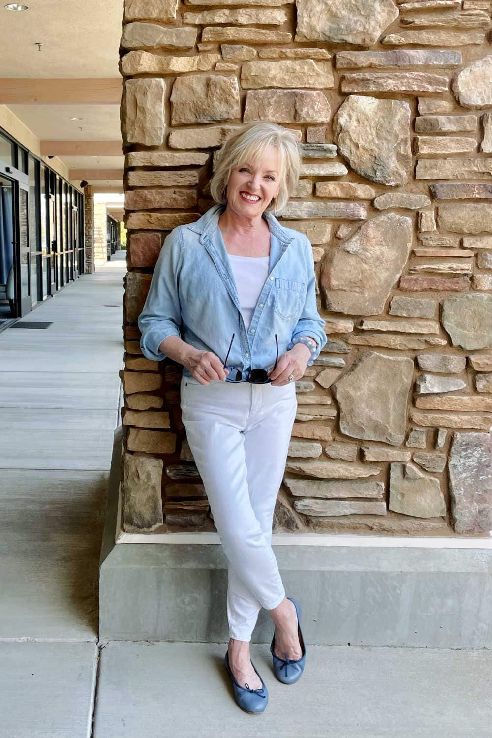woman leaning agains pillar wearing white denim jeans with chambray shirt and blue ballet flats