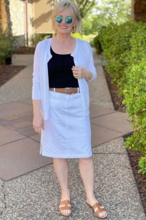 woman wearing white cardigan, black tank top and white denim skirt