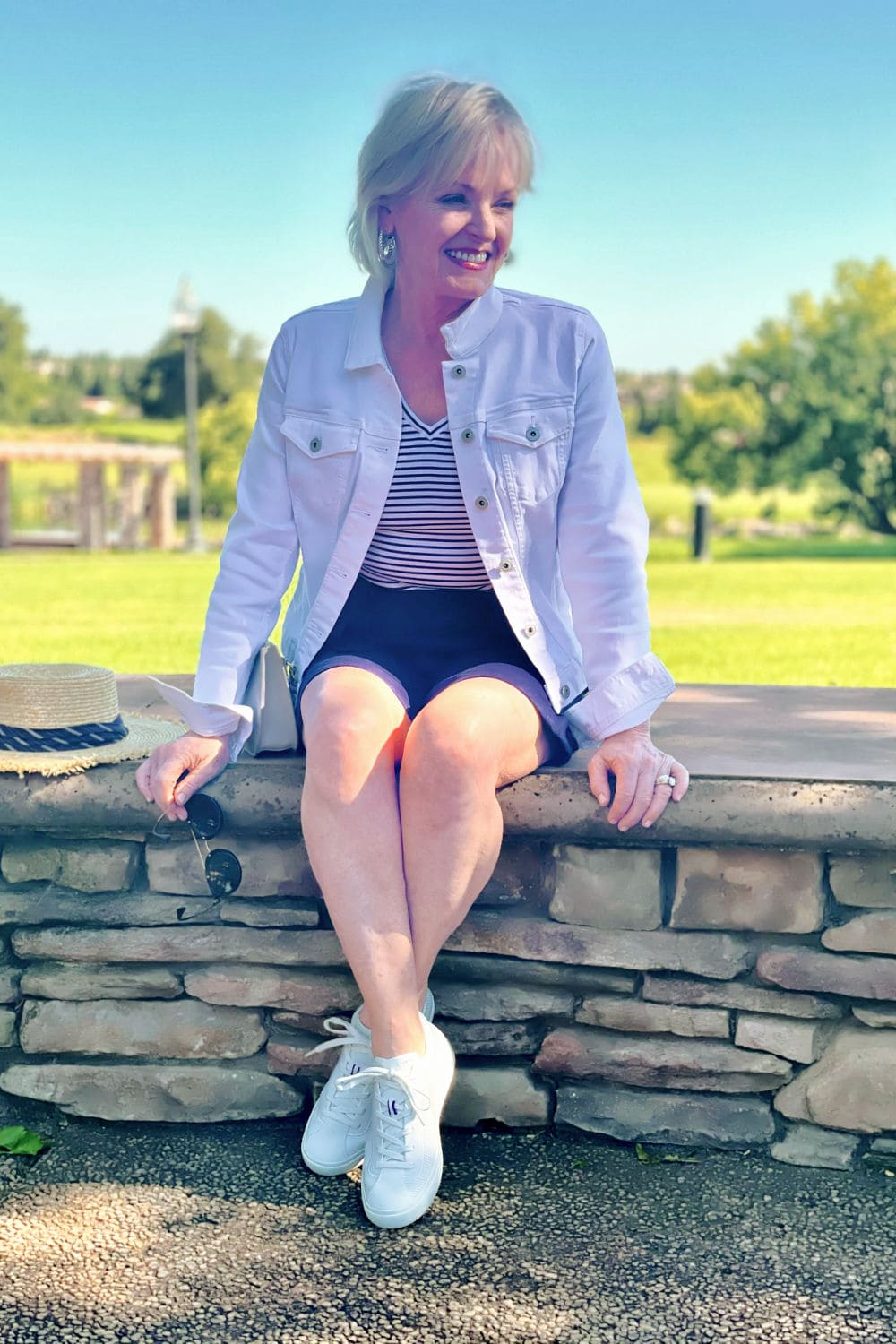 blonde woman sitting on wall wearing white denim jacket and striped tee